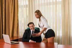 Сексуальная секретарша с таблеткой около босса в офисе Стоковые Фото