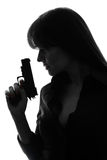 Сексуальная сыщицкая женщина держа силуэт пушки стоковые изображения