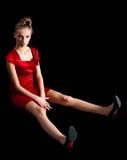 Сексуальная тонкая женщина в красном платье сидит на поле стоковое изображение