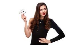 Сексуальное брюнет представляя с 2 карточками тузов в ее руках, изоляция вьющиеся волосы концепции покера на белой предпосылке стоковая фотография