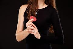 Сексуальное брюнет представляя с обломоками в ее руках, предпосылка вьющиеся волосы черноты концепции покера стоковые фото