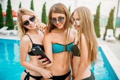 Сексуальные девушки в купальниках делают selfie около бассейна Стоковое Изображение