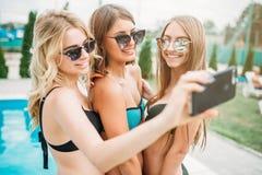 Сексуальные девушки в купальниках делают selfie около бассейна Стоковые Фото