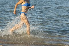 Сексуальные молодые женщина или девушка брюнета нося бикини бежать через прибой на дезертированном тропическом пляже с голубым не стоковое фото