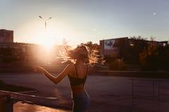 Сексуальные танцы девушки в городе на заходе солнца Стоковые Фото