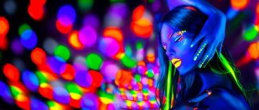 Сексуальные танцы девушки в неоновых светах Женщина фотомодели с дневным макияжем представляя в УЛЬТРАФИОЛЕТОВОМ стоковое изображение