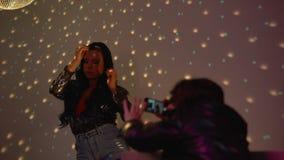 Сексуальные танцы девушки на партии в светах клуба, человеке неистовства снимая видео на смартфоне видеоматериал