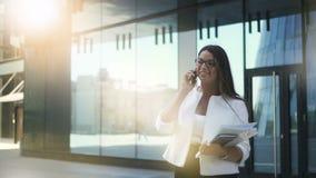 Сексуальный вождь коммерсантки банкира говоря на телефоне стоя на предпосылке здания в летнем дне видеоматериал