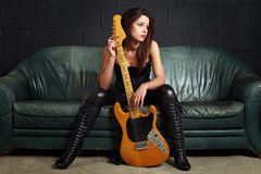 Сексуальный игрок гитары сидя на кресле Стоковое Изображение