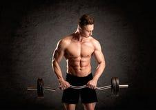 Сексуальный парень lifter веса показывая мышцы Стоковое Изображение