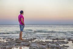 Сексуальный уменьшите подходящего человека брюнет в шортах голубых джинсов и фиолетовом пинке Стоковое Изображение