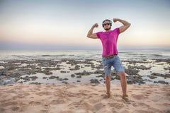 Сексуальный уменьшите подходящего человека брюнет в шортах голубых джинсов и фиолетовом пинке Стоковые Фото