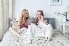 2 сексуальных белокурых девушки в pyjamas имея потеху в спальне Молодые женщины лежа в кровати используя таблетку Стоковые Изображения RF