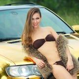Сексуальная дама около золотого автомобиля стоковое изображение rf