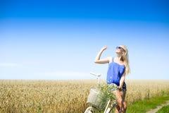 Сексуальная белокурая девушка на велосипеде при корзина смотря в небе Стоковые Фотографии RF