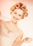 Сексуальная белокурая девушка при curlers в нижнем белье и шарики имея потеху Стоковая Фотография