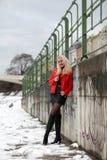 Сексуальная белокурая женщина в красной кожаной куртке и мини юбке Стоковые Изображения