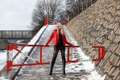Сексуальная белокурая женщина в красной кожаной куртке и мини юбке Стоковые Фотографии RF