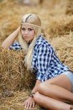 Сексуальная белокурая женщина отдыхая на сене в сельских районах Стоковая Фотография