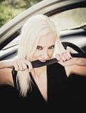 Сексуальная белокурая женщина сидя в автомобиле и сдерживая ремень безопасности. Крупный план Стоковое Изображение