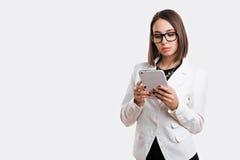Сексуальная бизнес-леди с стеклами с таблеткой на белой предпосылке Стоковая Фотография