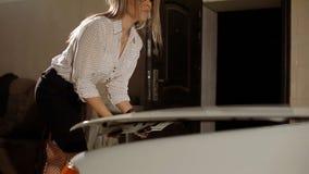 Сексуальная блондинка в стеклах и openwork колготки раскрывает клобук автомобиля сток-видео