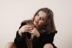Сексуальная блондинка девушки в черном мехе Стоковые Изображения