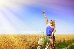 Сексуальная девушка возбужденная на белом велосипеде и указывать дальше Стоковое фото RF