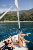 Сексуальная девушка в swimwear на яхте в тропиках Стоковая Фотография
