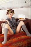 Сексуальная девушка есть спагетти на кресле Стоковая Фотография