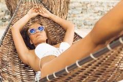 Сексуальная девушка ослабляет в гамаке на троповом пляже Стоковые Фото