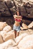 Сексуальная девушка раздевает на пляже утеса Стоковые Изображения