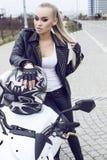 Сексуальная девушка с длинными светлыми волосами в кожаной куртке, представляя на мотоцилк Стоковое Фото