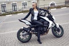 Сексуальная девушка с длинными светлыми волосами в кожаной куртке, представляя на мотоцилк Стоковая Фотография