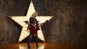 Сексуальная девушка с электрической гитарой в коже, светя сток-видео