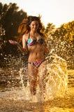 Сексуальная женщина брюнет в купальнике бежать в речной воде Сексуальная молодая женщина играя с водой во время захода солнца кра Стоковая Фотография