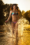 Сексуальная женщина брюнет в купальнике бежать в речной воде Сексуальная молодая женщина играя с водой во время захода солнца кра Стоковые Изображения RF