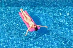 Сексуальная женщина брюнет загорая на раздувном тюфяке в плавать p стоковое изображение rf