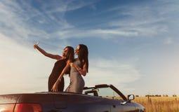 Сексуальная женщина брюнет 2 стоя близко cabriolet на дороге Стоковые Фотографии RF