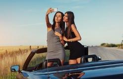 Сексуальная женщина брюнет 2 стоя близко cabriolet Стоковое Фото