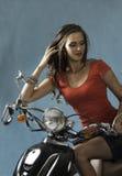Сексуальная женщина брюнет усаженная на мотоцикл стоковое фото