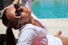 Сексуальная женщина загорая на курорте бассейна Стоковая Фотография