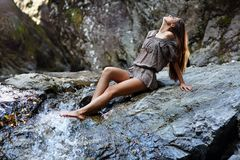 Сексуальная женщина кладя около водопада Стоковые Изображения