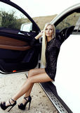 Сексуальная женщина при светлые волосы представляя в роскошном автомобиле Стоковое Изображение