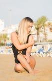 Сексуальная женщина сидит на песчаном пляже в черном купальнике Стоковое Фото