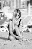 Сексуальная женщина сидит на песчаном пляже в черном купальнике Стоковые Изображения RF