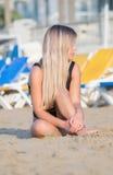 Сексуальная женщина сидит на песчаном пляже в черном купальнике Стоковая Фотография