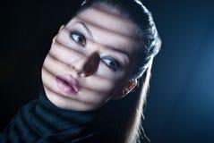 Сексуальная женщина смотря через окно с jalousie стоковые фото