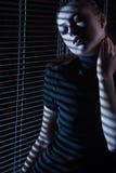 Сексуальная женщина смотря через окно с jalousie стоковая фотография