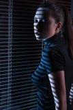 Сексуальная женщина смотря через окно с jalousie стоковые изображения rf